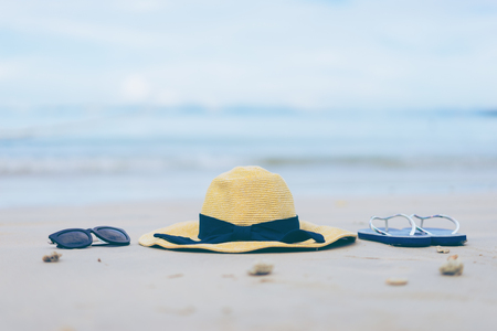 Flip-flops, beach hat and sunglasses on the sand. Summer vacation concept 스톡 콘텐츠