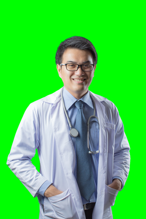Portrait of confident young asian handsome doctor isolated on green background