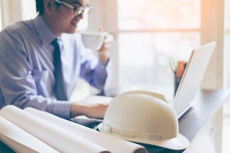 젊은 아시아 엔지니어 랩톱 컴퓨터와 사무실에서 안전 헬멧 작업. 행복 한 엔지니어 마시는 커피 및 작업 프로젝트입니다.