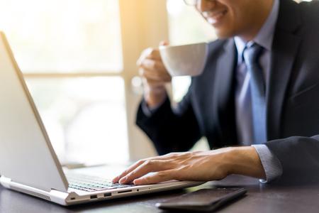 사무실 책상에 커피 한잔과 함께 자신의 노트북을 사용하는 젊은 행복 사업가. 사무실에서 랩톱을 사용하는 비즈니스 사람 (남자)의 초상화. 스톡 콘텐츠