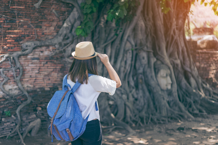 Young woman traveler with backpack and hat looking the Head of the Buddha, with tree trunk and roots growing around it. Wat Mahathat temple, Ayutthaya near Bangkok Thailand. Traveling in Ayutthaya