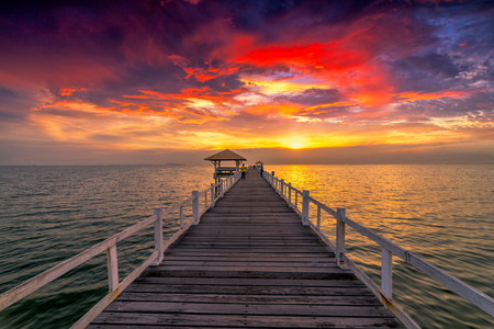 Traveler standing on wooden bridge in the sea at sunset scence Фото со стока