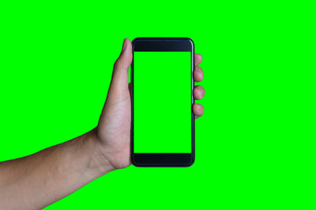 Mans hand shows mobile smartphone with green screen in vertical position isolated on green background - mockup template and clipping path