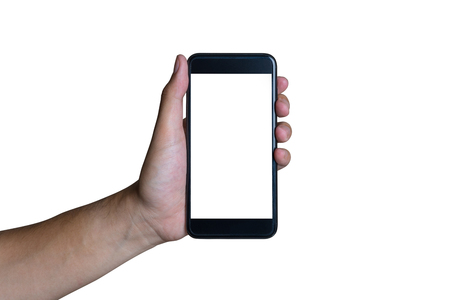 Mans hand shows mobile smartphone with green screen in vertical position isolated on green background Фото со стока