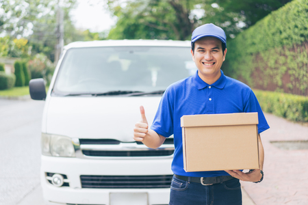Delivery concept - Smiling happy young asian handsome man show thumbs up and postal delivery courier man in front of cargo van delivering package holding box with service mind and blue uniform