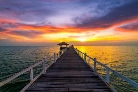 旅行者站在木橋在海中在夕陽的陰霾