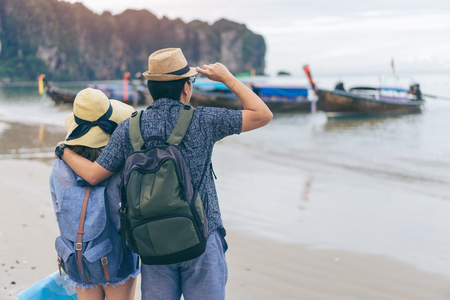 Young love couple traveler with backpack and hat holding map at the sea with long boat thailand background from Ao Nang Beach Krabi. Traveling in Krabi Thailand , Traveler summer concept 스톡 콘텐츠
