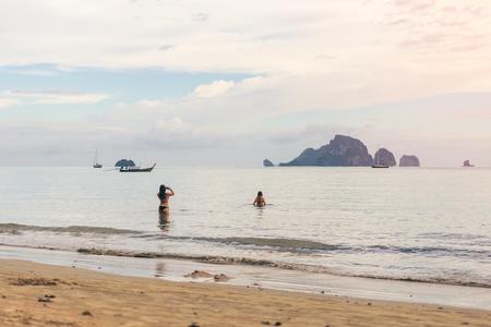 年輕女子旅行者在海上拍攝兩件,拍攝了奧南海灘甲米的照片。旅行在甲米泰國,旅客夏天的概念 版權商用圖片