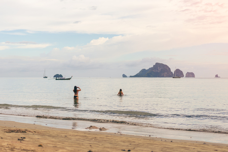 Young women traveler with two pieces at the sea take a photo from Ao Nang Beach Krabi. Traveling in Krabi Thailand , Traveler summer concept Фото со стока