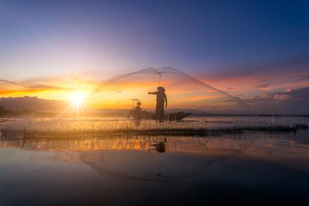 亞洲漁夫漁船在早晨在泰國在湖上釣魚