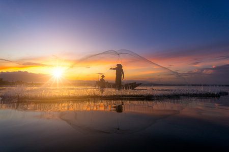 Asian Fisherman fishing nets on the boat fishing at lake in morning at Thailand Фото со стока