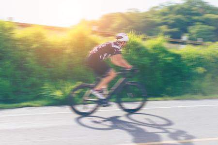 Motion расплывчатый счастливый человек, езда на велосипеде открытый велотренажер пути в первой половине дня