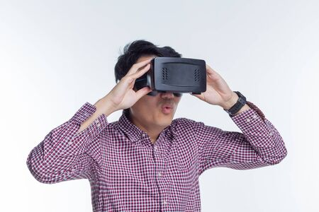Возбужденный человек, испытывая виртуальную реальность через VR-гарнитуру и касаясь что-то своими руками на белом фоне Фото со стока