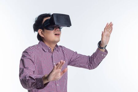 Excited man experiencing virtual reality via VR headset and touching something with his hands on white background Фото со стока