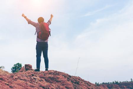 Походы человек скалолазание, альпинист или бегун в горах, вдохновляющий пейзаж. Мотивированный hiker с красным рюкзаком, глядя на прекрасный вид. Поход, путешествия и туризм. фитнес Фото со стока