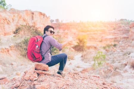徒步旅行者攀岩豎起大拇指的動作,登山者或山腳跑步者,靈感景觀。激動的遠足者與紅色背包看著美麗的景色。徒步旅行者概念 版權商用圖片