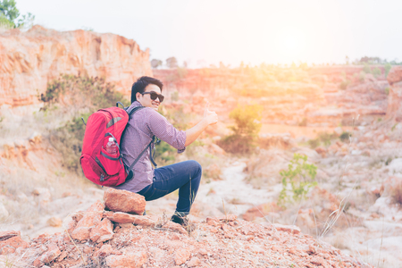 Hiking man rock climbing thumbs up action , climber or trail runner in mountains, inspirational landscape. Motivated hiker with red backpack looking at beautiful view. Trekking, traveler concept