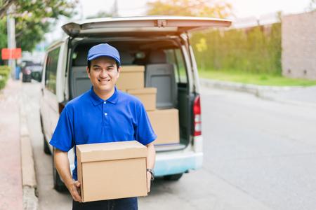 交付概念 - 微笑快樂的年輕亞裔英俊的男人郵遞快遞人員在貨物的後面提供包裹保持箱與服務頭腦和藍色制服