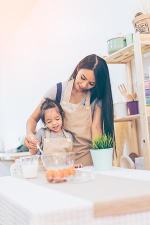 幸福的家庭在廚房裡。母親和孩子的女兒做飯準備麵團,在廚房裡烘烤餅乾