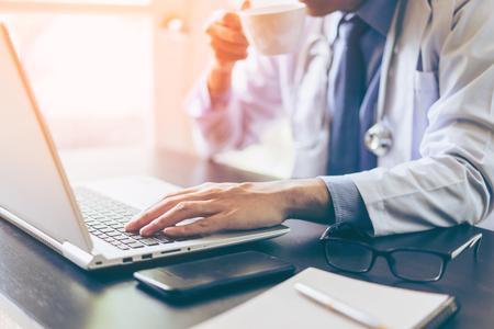 醫生的手用筆記本電腦在工作台上喝咖啡