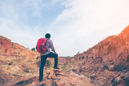 Hiking man rock climbing, climber or trail runner in mountains, inspirational landscape. Motivated hiker with red backpack looking at beautiful view. Trekking, travel and tourism concept. Fitness