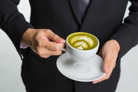 Руки бизнесмена, проведение чашку кофе или зеленый чай на белом фоне Фото со стока