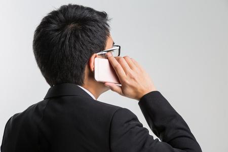 經營理念:亞洲英俊的商人微笑和白色背景上的智能手機交談