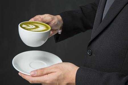 Руки бизнесмена, проведение чашку кофе или зеленый чай на сером фоне