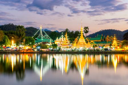 屈Jongklang寺日落李宗紅 - 屈Jongkham寺廟遊客最喜歡的地方靠近清邁,泰國湄宏順反映水的天空