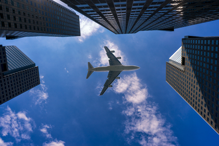 Commercial airplane flying over modern building in Singapore city downtown