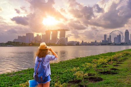 年輕女子旅行者與天空藍色背包和帽子拿著地圖與新加坡市中心背景。在日落時間在新加坡旅行 版權商用圖片