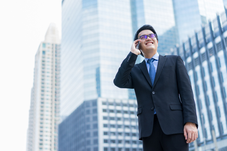 年輕的亞裔英俊的商人和眼鏡使用智能手機微笑在商業區