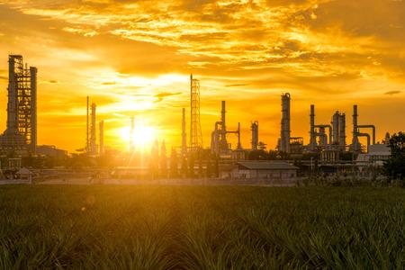 Восход солнца завода нефтеперерабатывающего завода с голубого неба и облаков. Нефтехимический завод, Нефть, Промышленное производство. Фото со стока