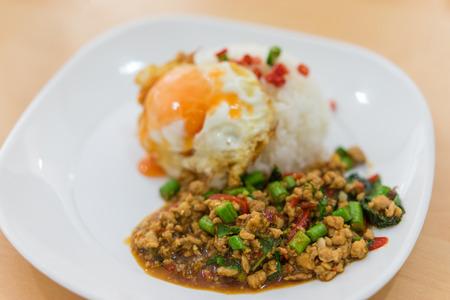 Риса увенчана жареной жареной свининой и базиликом и обжигом яйца. Селективный фокус свинины, Популярная тайская кухня