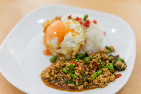 Rice topped with stir-fried pork and basil and fired egg. Selective focus pork, Popular Thai food