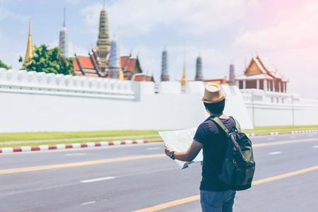 與背包和帽子的年輕男子旅行者在曼谷泰國與大皇宮和Wat Phra keaw尋找地圖。旅行在曼谷泰國 版權商用圖片