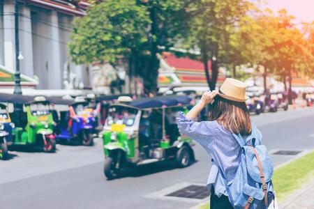 Молодая женщина путешественник с голубой рюкзак и шляпа ищет путь с tuk tuk Таиланд фон из wat pho в Бангкоке Таиланд. Путешествие в Бангкок Таиланд