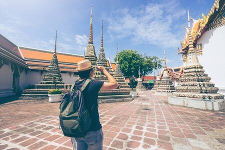 年輕男子旅行者背包和帽子看泰國曼谷Wat Pho的建築。旅行在曼谷泰國