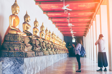 年輕女子旅行者與背包尊敬或祈禱許多佛像在Wat Pho泰國曼谷。旅行在曼谷泰國