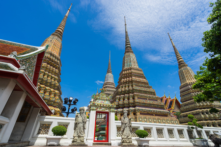 Ancient Stupas and pagoda in Wat Pho temple in Bangkok Thailand with blue sky and clouds. Traveling in Bangkok Thailand