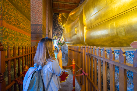 Young woman traveler with backpack respecting or pray at reclining buddha in Wat Pho at Bangkok Thailand. Traveling in Bangkok Thailand Фото со стока