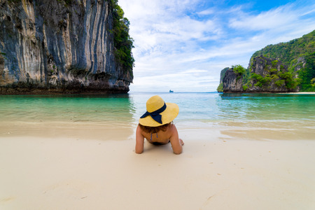 Young women wearing bikini relaxing and hat is lying on topical beach at Hong Island Krabi Thailand.
