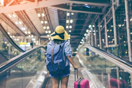 Молодая женщина путешественник в международном аэропорту с рюкзак, холдинг чемодан или багаж в руке, Красивая молодая турист девушка с рюкзак и осуществлять багаж в аэропорту терминал, на travelator