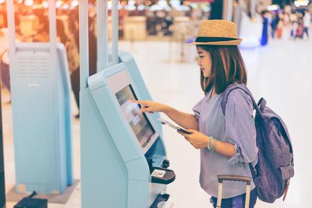 年輕女子旅行者在國際機場與背包拿著手提箱或行李和護照在她的手使用機場在機場的自助服務