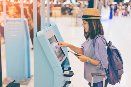 Young woman traveler in international airport with backpack holding suitcase or baggage and passport in her hand using self service check in machine at airport