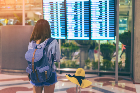 Young woman traveler in international airport looking at the flight information board holding suitcase or baggage in her hand, checking her flight at the airport terminal. 스톡 콘텐츠