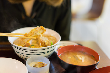 Woman hands eating katsudon or tonkatsu set with miso soup in bowl on restaurant Фото со стока