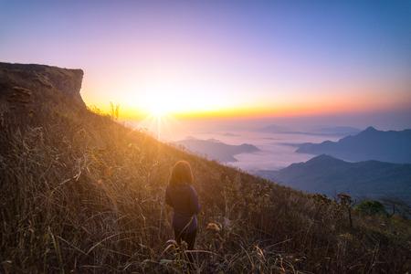 女子旅遊者是泰國中國古代旅遊者,在Phu chi fa山脈和雲景山峰。女人旅行者站在日出時看起來漂亮的霧。遠足徒步旅行的概念