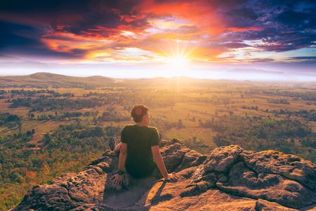Молодой человек путешественник в зеленой спортивной одежде сидит на краю скалы и, глядя на туманную долину рев с Vintage тон.