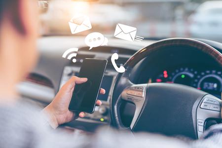 Homme utilisant un smartphone en conduisant la voiture - concept de transport et de véhicule avec l'icône de médias sociaux Banque d'images - 81858778